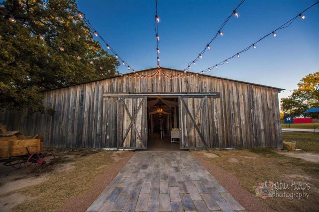 Wooden Anding Acres Wedding Venue   barn with lights and texas flag