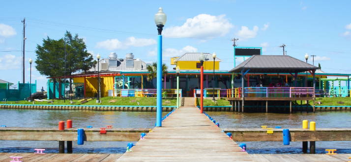 wooden dock on cedar creek lake leading to colorful building painted yellow red teal green pink